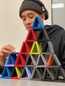 young man playing with feltiles from archKIDecture