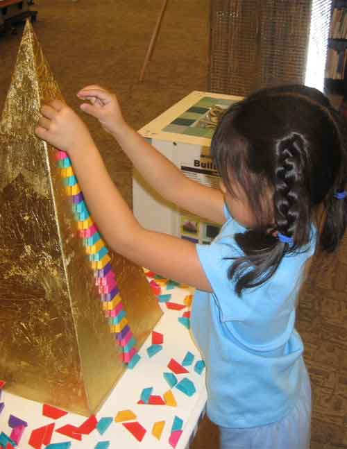 Girl playing with Golden pyramid module at the BuildIT! exhibit about architecture for kids